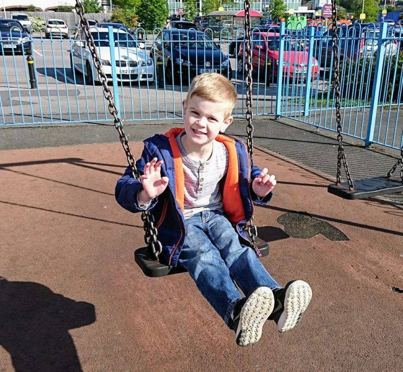 Little Man waving on swing